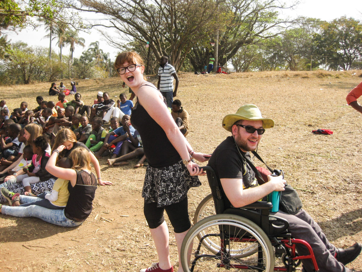 Crossing Countries volunteer in a wheelchair is pulled backwards by non disabled team member while supporting kids from Bobbi Bear in South Africa