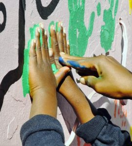 A painted hand helps press smaller hands to make a hand print on the Mason Lincoln mural