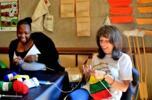Jean teaching Thenjiwe to knit at Mason Lincoln Special Needs School