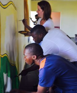 The team painting a mural at Ikwhezi Wefare Organisation